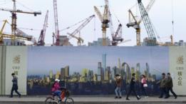 Personas caminando y pedaleando frente a una construcción.