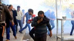 أحد المتظاهرين في بغداد يغطي وجهه بعد اطلاق قوات الأمن الغاز المسيل للدموع