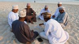 Un grupo de habitantes de Omán jugando cartas en una playa