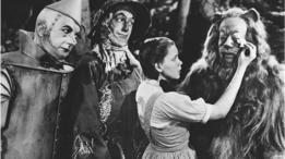 Cuadro de la película el mago de Oz. Dorothy enjuga las lágrimas del león. Observan el espantapájaros y el hombre de hojalata.