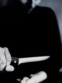 Mujer acercando un cuchillo a su muñeca