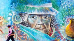 Una persona camina frente a un colorido grafiti en Ecuador