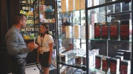 Una vendedora de perfumes con un cliente.