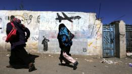 El 24 de diciembre de 2016 dos mujeres yemeníes pasan frente a un graffiti en Saná, pintado en protesta de los ataques con drone de Estados Unidos.