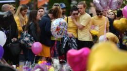Un grupo de personas colocan flores y globos en memoria de las víctimas del atentado en el Manchester Arena.