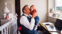 Un hombre sentado frente a su laptop, cargando y besando a un bebé