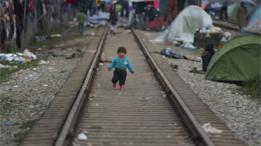 طفل مهاجر يمشي على قضبان القطار شمال اليونان