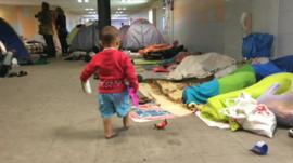 Young child and migrants sleeping in Keleti station subway