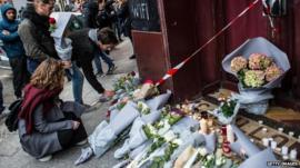 People leave floral tributes at the main entrance of Le Carillon restaurant on November 14, 2015 in Paris