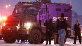 A police vehicle carries a suspect away after a shooting at a Planned Parenthood clinic Friday, Nov. 27, 2015, in Colorado Springs, Colorado