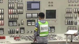 Worker standing in front of control panel at Sendai plant