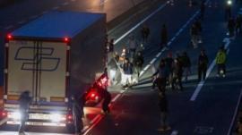 Refugees wielding sticks attack lorries