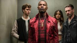 Three men and a woman standing - a scene from Baby Driver