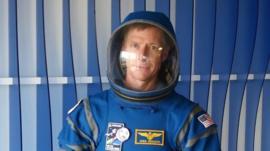 A man wearing a blue spacesuit