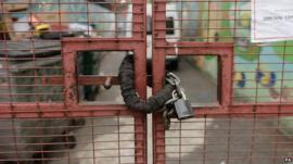 Close up of padlock on closed gate at Kids Company building in Camberwell, London