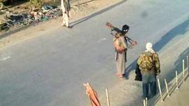 Taliban fighters walk on a street in Kunduz