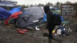 A migrant walks in a muddy field in a camp of makeshift shelters for migrants