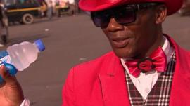 Farai sells water wearing a pink jacket with matching hat and bow tie