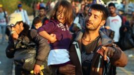 Migrants cross the border between Hungary and Austria