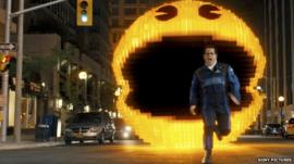 A scene from Pixels - a man is being chased by Pac Man