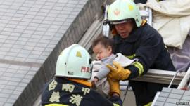 Rescue workers remove a baby from the site where a 17-storey apartment building collapsed after an earthquake hit Tainan,