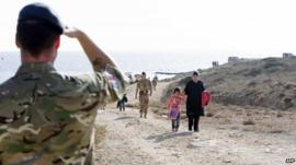 British Military personnel escort migrants who arrived by boat away from the shore