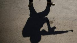 The shadows of rebel fighters carrying fake weapons
