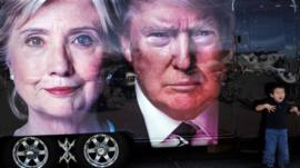 A boy gestures next to a backdrop of US Democratic presidential nominee Hillary Clinton and her Republican counterpart Donald Trump at the Hofstra University, in Hempstead, New York