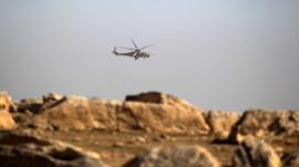 An army military helicopter flies over the Iraqi rapid response forces position during a battle against Islamic State militants in the south of Mosul, Iraq