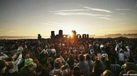 A large crowd are standing in front of Stonehenge as the sun rises on the summer solstice