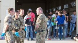 Syrian migrants are temporarily housed at a warehouse after coming ashore at RAF base Akrotiri in Cyprus.
