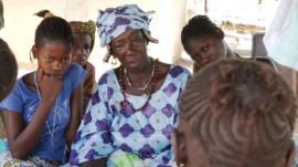 Egge Kande sitting with village girls.