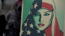 Demonstrators holds a placard showing a woman wearing a veil with the US flag
