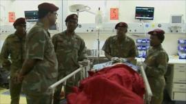 Soldiers by a patient's bedside