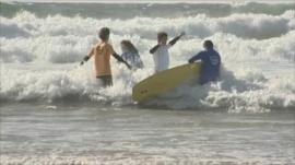 NHS patients in the sea with surf boards