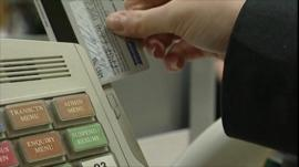 A credit card being swiped at a till