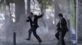 People dodge falling debris as they evacuate an office building
