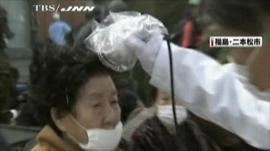 A Japanese woman is tested for signs of radiation