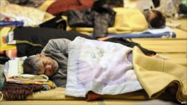 A man asleep on the floor of a relief centre