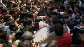 Upset supporters of Maulvi Showkat Ahmed Shah surround his shrouded body