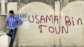 Man next to graffiti on wall