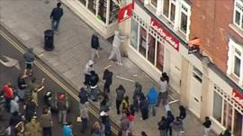 Hooded man attacking window of betting shop in Hackney