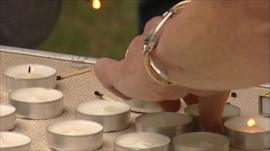 Local residents lighting candles at vigil for Richard Bowes