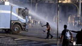 Rioter throws missile at water cannon truck