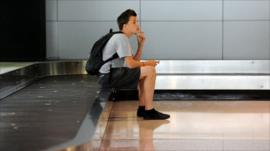 A traveller waiting for luggage at the Qantas baggage carousel after flight cancellations at Sydney Airport on October 10, 2011