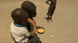 Children carrying food aid in Kenyan drought relief camp