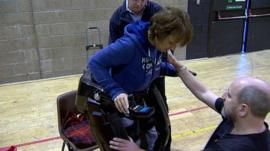 Elena Bertoldo is helped into the bionic legs by Richard Little