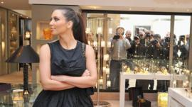 Kim Kardashian flanked by cameras