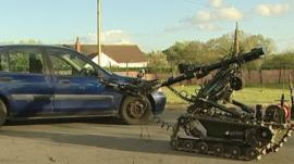 Bomb disposal robot approaches car