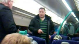 Man pointing at alleged fare-avoider on train